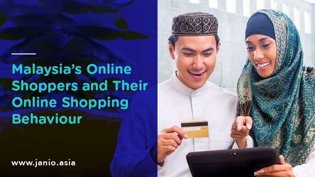 Muslim couple shopping online together, with lady happily pointing at the screen while the male holds onto his credit card